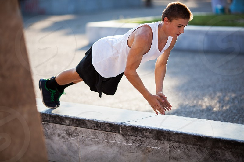 Young sportive man doing push-ups on border stone in the city. Urban exercising and training photo