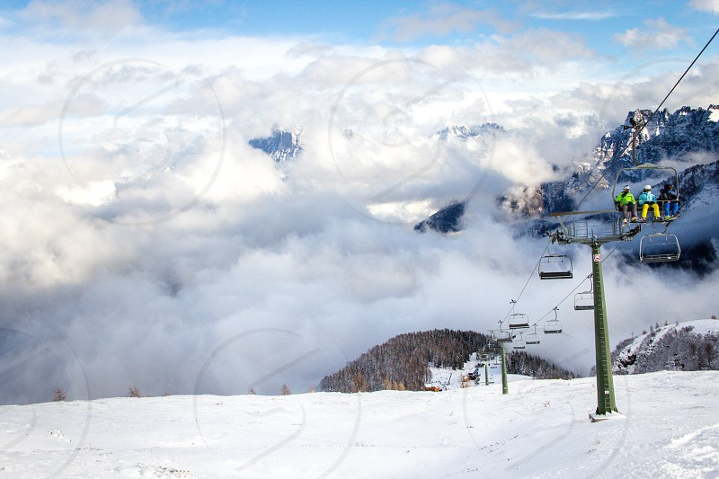 Skiers above the clouds at the San Pellegrino Ski Area in Italy's Dolomite Alps photo