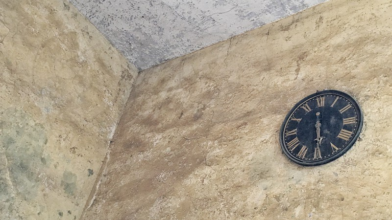 Clock hung high up on run-down plastered wall photo
