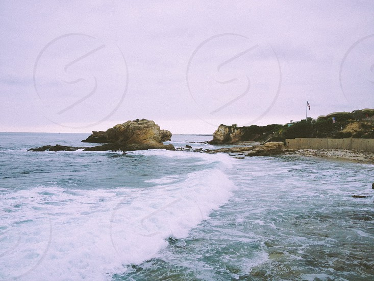 rocky mountain by the ocean in the cloudy sky photo