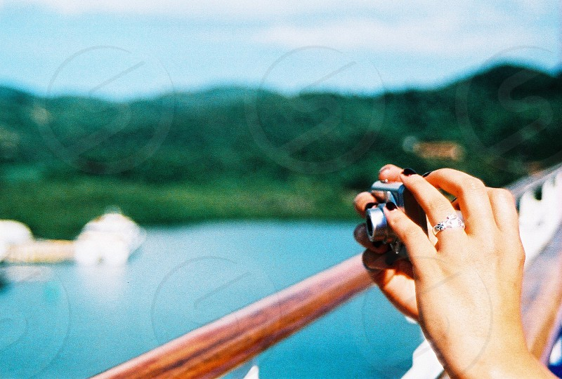 person holding black point-and-shoot camera near green mountain under white and blue sky during daytime photo