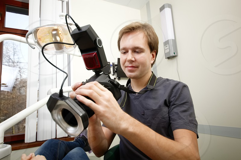 Young male dentist with camera making shots of patients smile after treatment photo