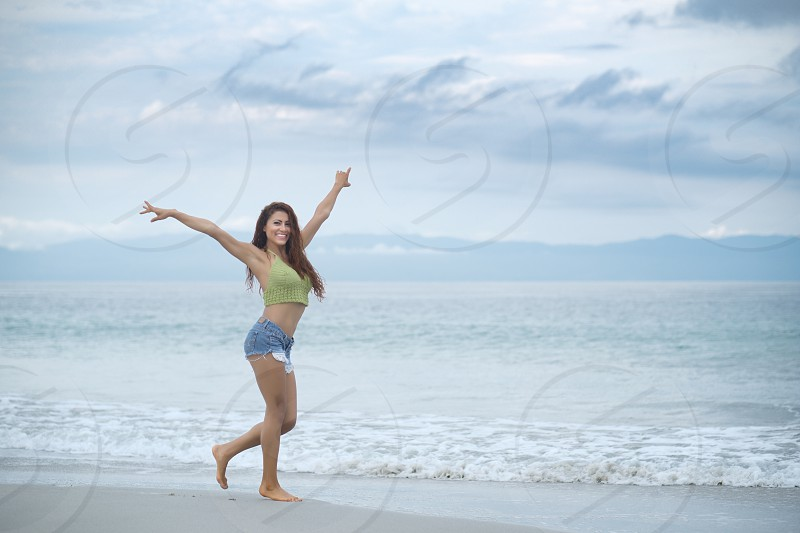Happy hispanic woman enjoying beach walk photo