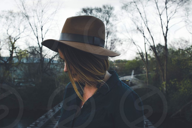 woman wearing blouse and fedora hat walking on bridge near forest during daytime photo