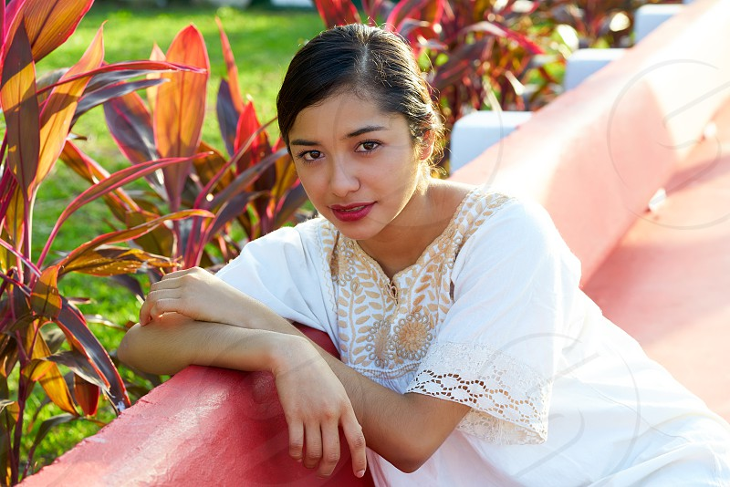 Mexican latin woman with ethnic dress sitting in garden park bench photo