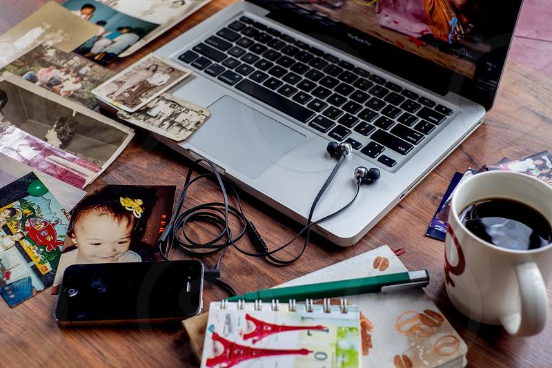 Macbook pro beside white ceramic mug on brown parquet surface photo