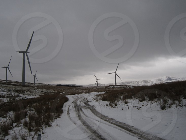 A snowy track leading to a wind farm... photo