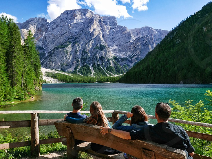 Four friends sitting on a bench and admiring the nature around them. Green lake surrounded by mountains. photo