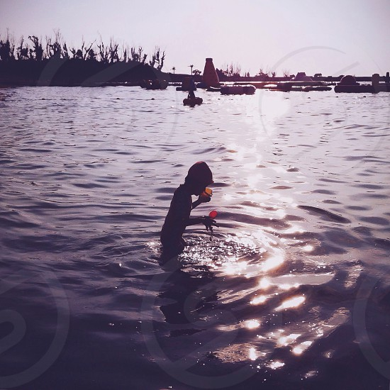 child playing on the body of water photo