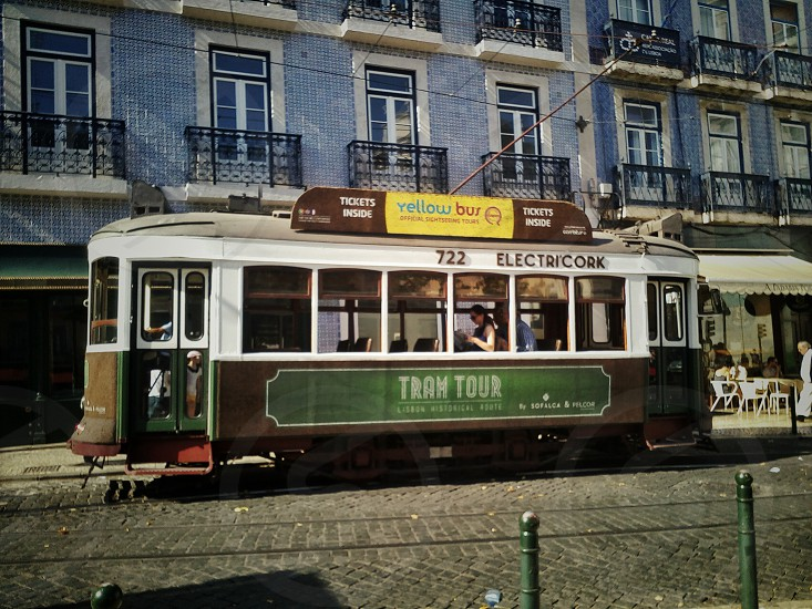white and brown tram tour travelling street during daytime photo