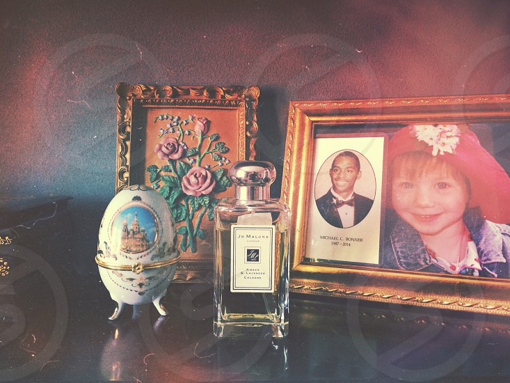 perfume glass egg and frames on dresser photo
