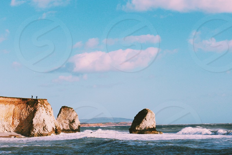 cliff on seashore under white and blue sky during daytime photo