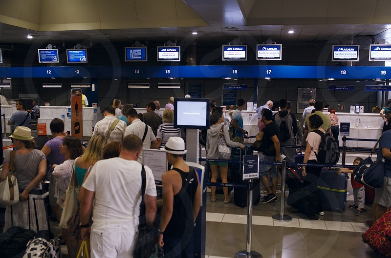 THESSALONIKI GREECE - AUGUST 8 2013: Departures hall at an airport with passengers queuing with their luggage to book in at the airline counters photo