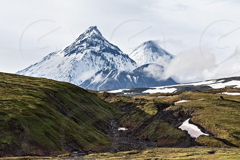 Nature of Kamchatka - picturesque volcanic landscape: view on Kamen Volcano active Klyuchevskoy Volcano (Klyuchevskaya Sopka) and active Bezymianny Volcano. Russia Far East Kamchatka Peninsula. photo