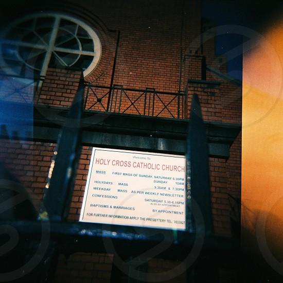 close photo of holy cross catholic church signage photo