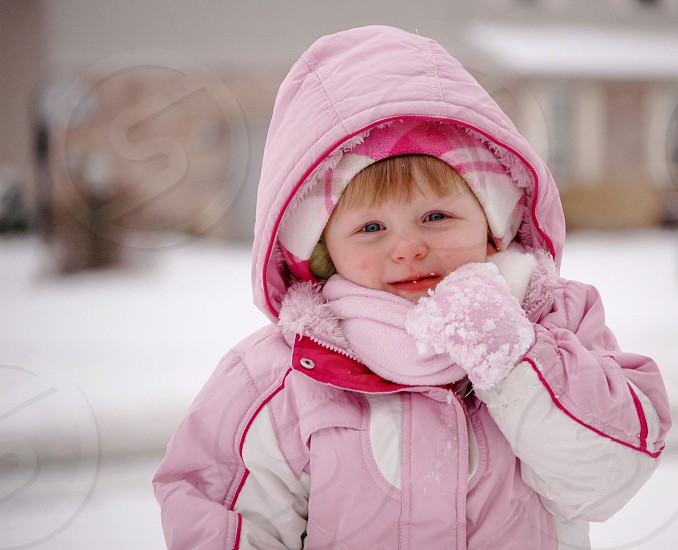 Young girl bundled up in the winter snow.  Winter young girl bundled snow cold pink kid photo