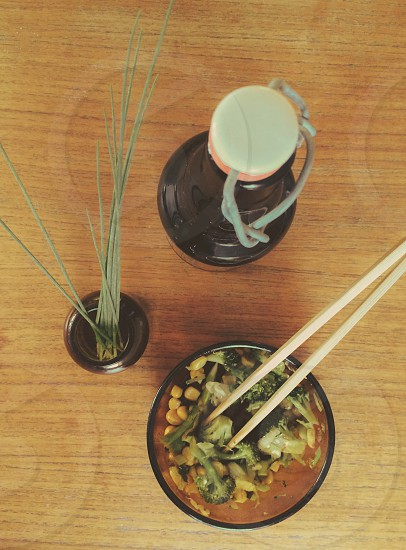 wood chopsticks in a bowl with broccoli and corn next to a drink bottle and green grass photo