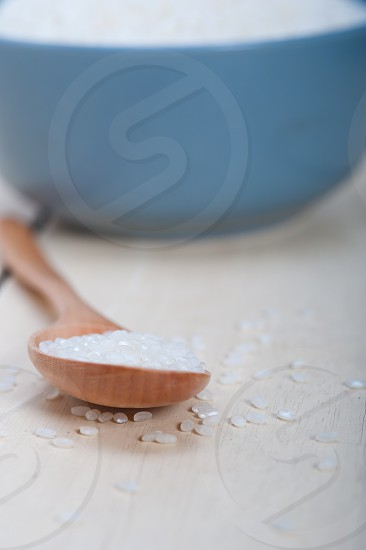 raw white rice on wood spoon and blue bowl extreme close up photo