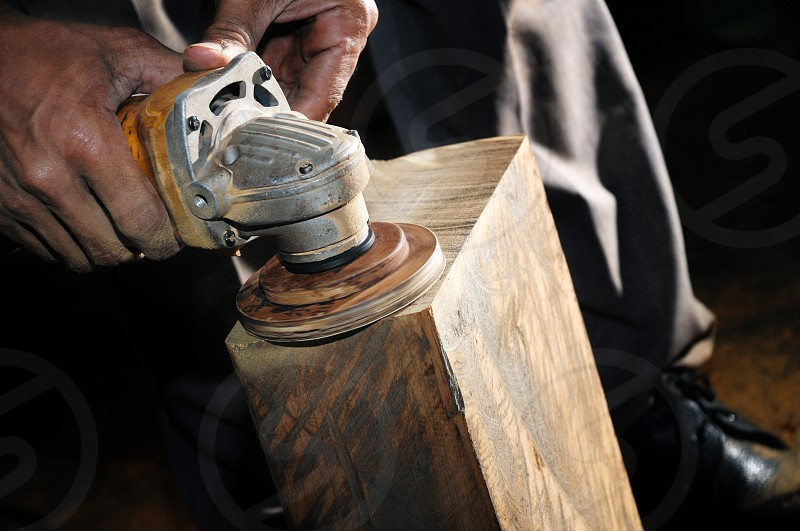 Closeup of carpenter sanding wood block with power wood sander. photo