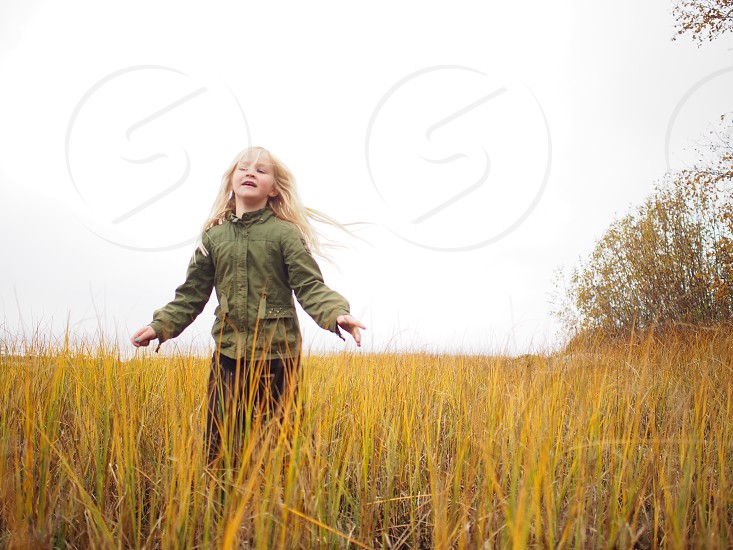 Young girl running tall grass autumn fall happy child kid photo