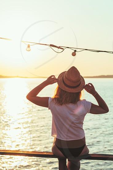 Young woman enjoying sunset at a beach bar photo