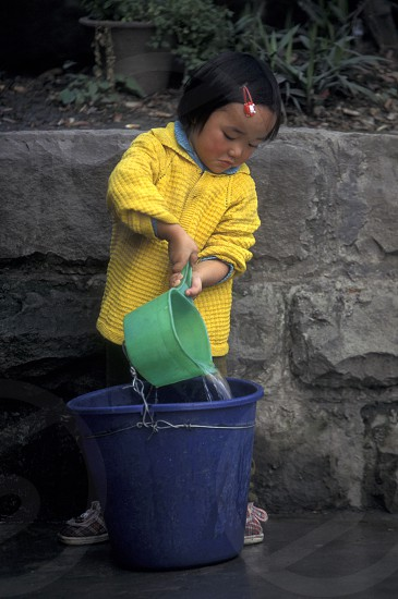 a girl get water at the main square in the city of Chongqing in the province of Sichuan in china in east asia.  photo