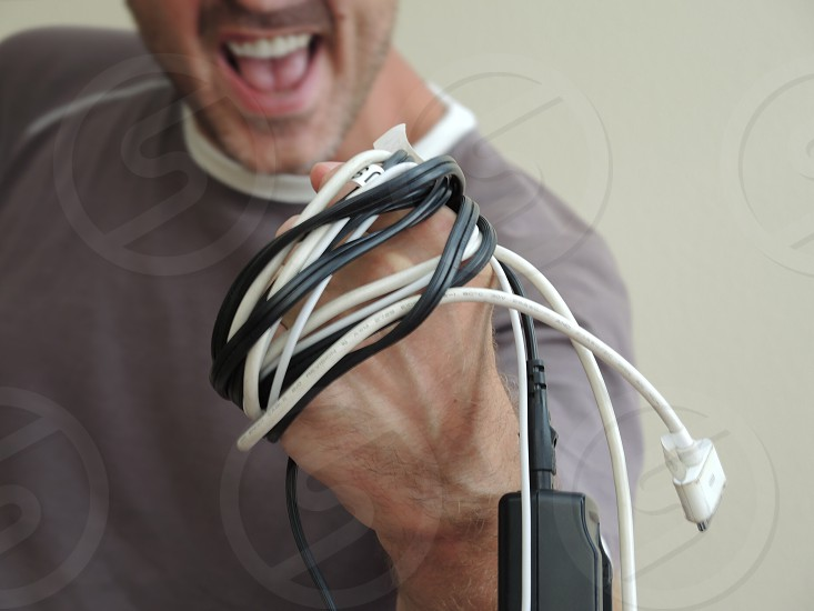 man holding black and white coated wires photo