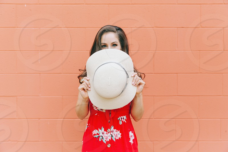 A beautiful young woman covering her face with a summer hat. photo
