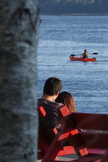 millenials water sitting on a bench nature date ocean kayak observe  romance summer Shelburne  Nova Scotia Canada photo