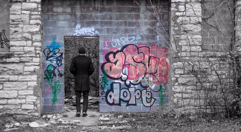man in black suit standing in front of graffiti covered wall photo