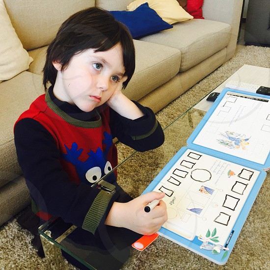 toddler day dreaming while doing his homework photo