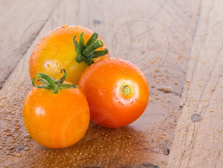 Macro close up of three organic tomatoes on an outdoor wooden table or bench and covered with light rain or dew to show they are just picked from plant photo