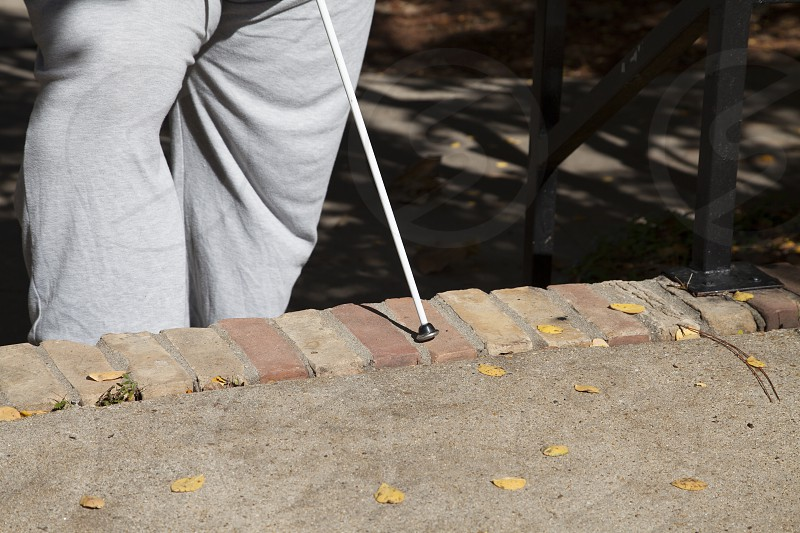 Blind person using a walking cane to navigate steps photo