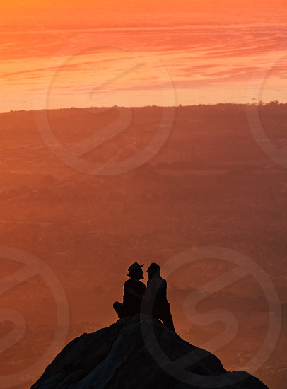 silhouette of 2 person during orange sunset photo