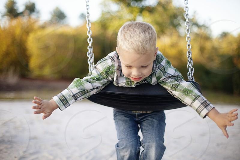 boy riding swing photo