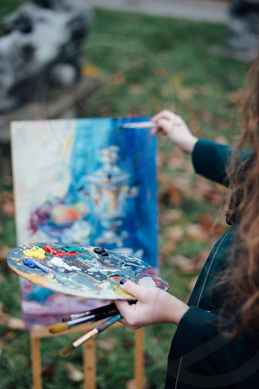 Pretty girl painting in the park  photo