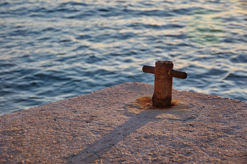 Closeup of concrete dock with metal wedge against the blue sea  in sunset photo