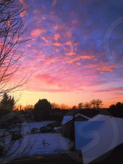 sunrise cloudy sky over snow covered houses photo