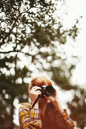 Girl red hair flannel bokeh Sony green trees woman  photo