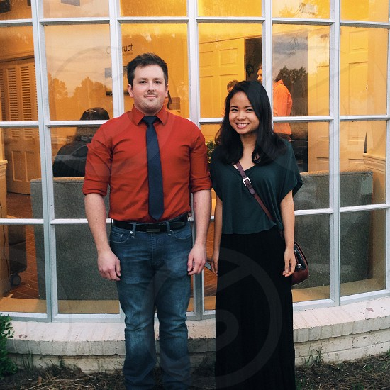 Man and Woman Standing Together in Front of Glass Windows photo
