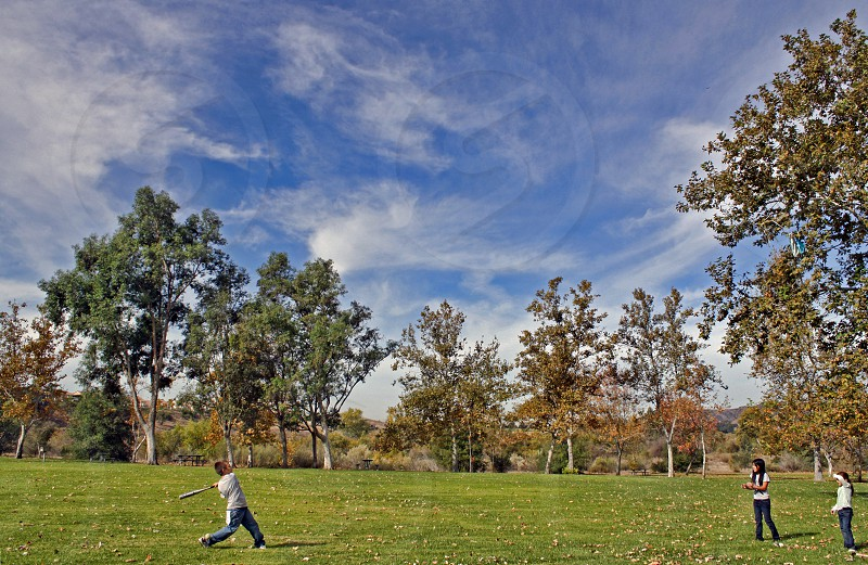 Seen in the distance three children play baseball in an open field in a park photo