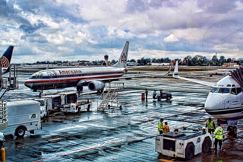 Airplanes line up on a wet airport tarmac photo