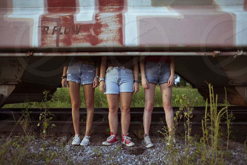 3 women in blue daisy dukes and white red sneakers photo