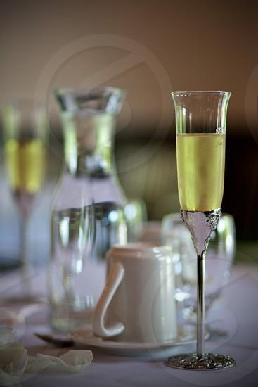 wine glass beside a plate of white mug photo