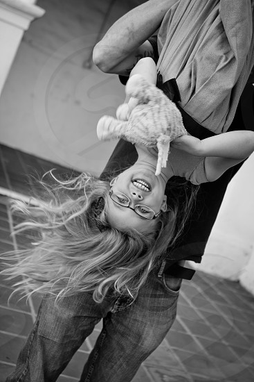 girl being flip upside down bu a man in black shirt and blue jeans photo
