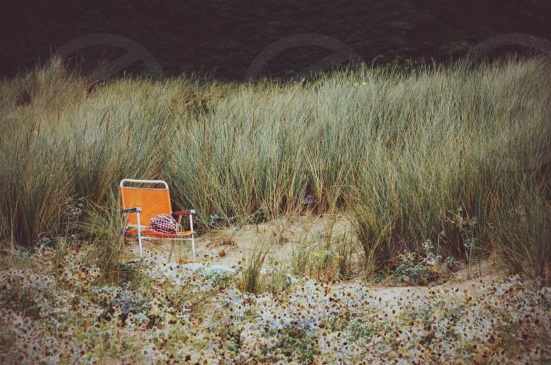 orange folding chair on brown sand surface photo