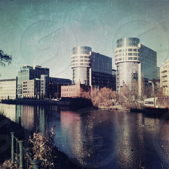 rounded glass buildings behind waterway  photo
