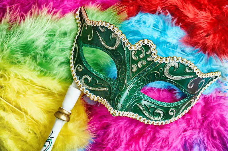 Close-up the green carnival mask Venetian mask (Opera mask) with white wood handle on the colorful soft fluffy feathers in yellow pink blue red and green Fantasy concept Photo booth props photo