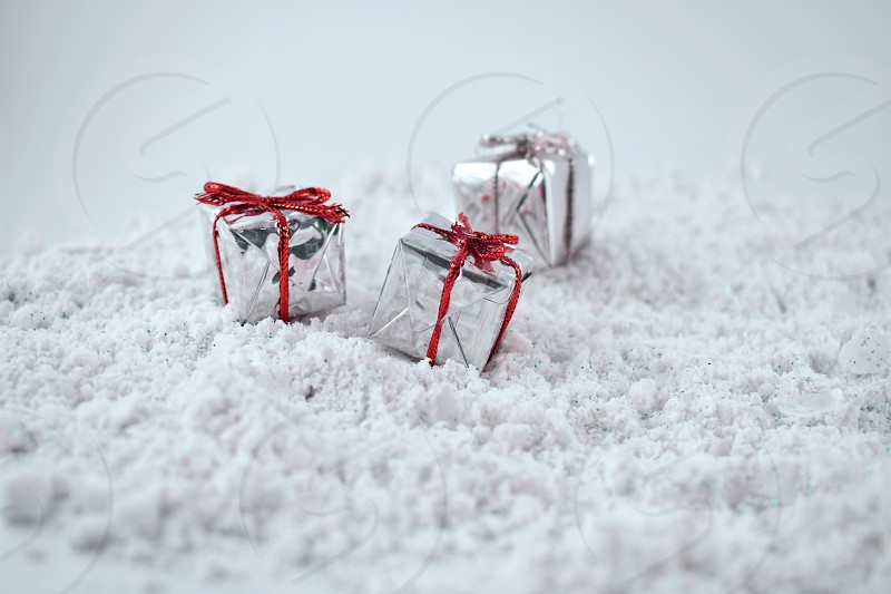 Christmas presents on a snow background. Silver holiday background with gifts. Christmas gift boxes. Silver decorations on shiny background with copy space for text photo