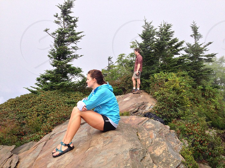 two figures on grey rocks over looking forest landscape photo